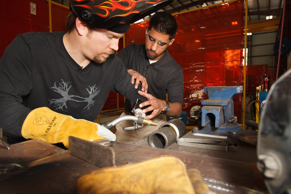 Upper Limb Occupational Therapist Joby Varghese helps Sky Carr position his body-powered prosthesis for welding