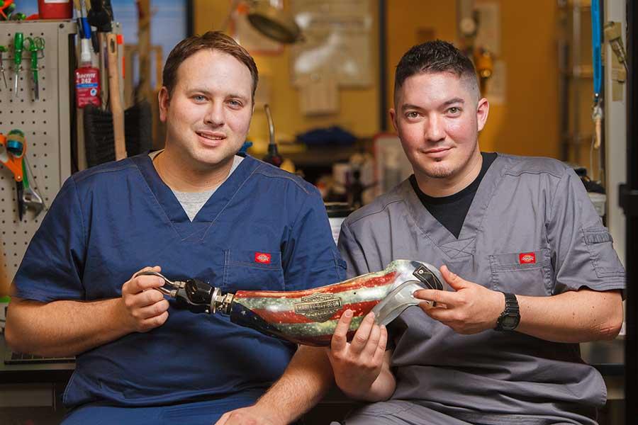 Arm Dynamics technicians holding a custom prosthesis