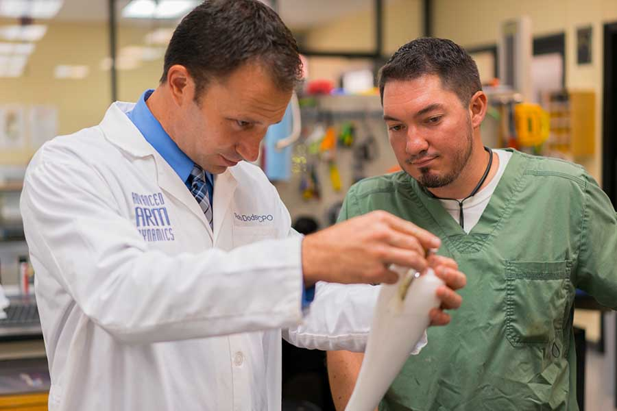 Arm Dynamics upper limb prosthetist and technician working on prosthesis