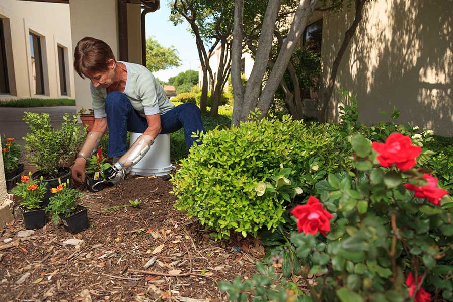 Arm Dynamics patient working in her garden