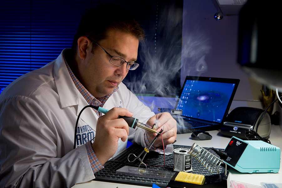 Arm Dynamics prosthetist working on prosthesis electronics