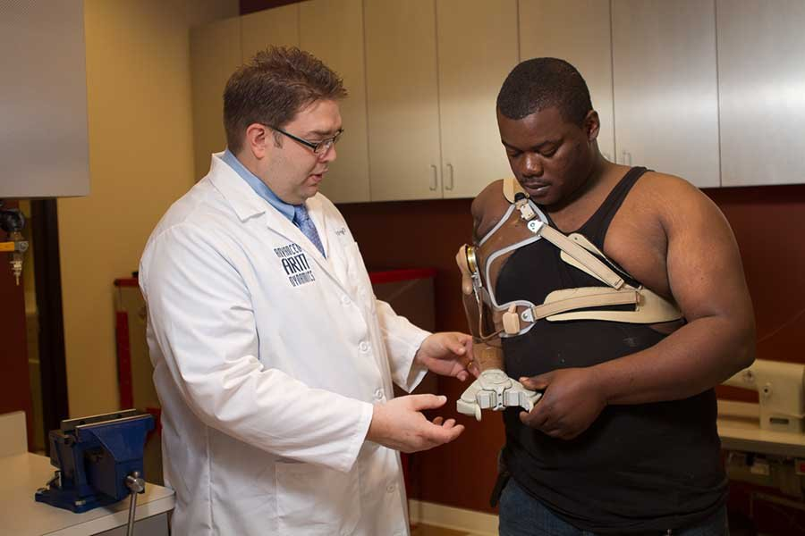 Arm Dynamics prosthetist working with a patient in the therapy room