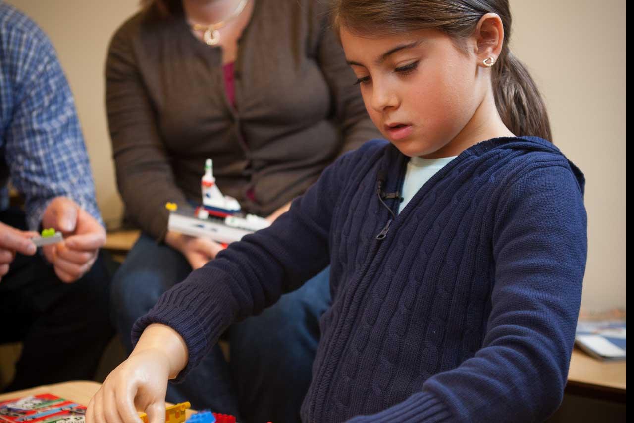Pediatric patient Alexia plays with logos