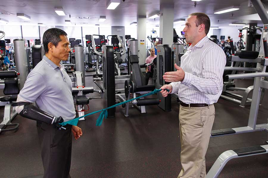 Therapist Chris Bollinger works with a patient in the gym