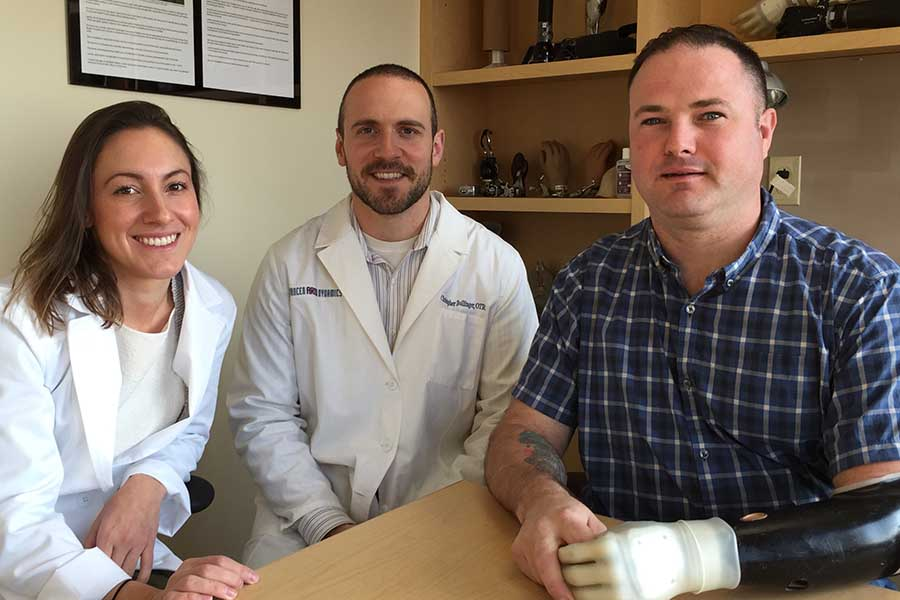 Prosthetist Michelle Intinelli and Therapist Chris Bollinger pose with a patient