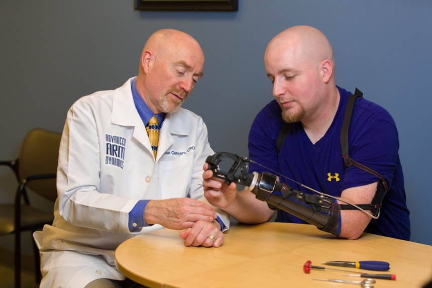Arm Dynamics prosthetist instructing patient on proper usage of his body powered prosthesis