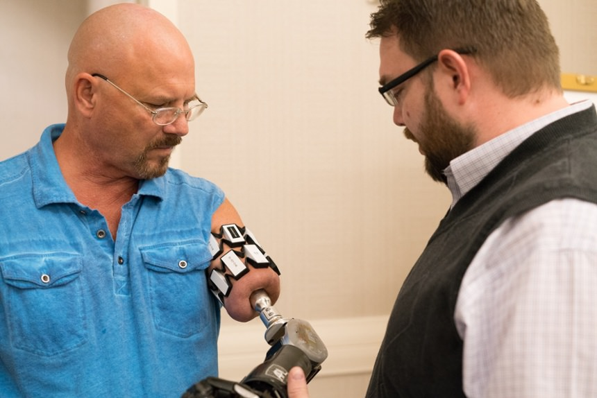 Arm Dynamics prosthetist speaking with an osseointegration amputee  at Arm Dynamics' upper limb prosthetic symposium event