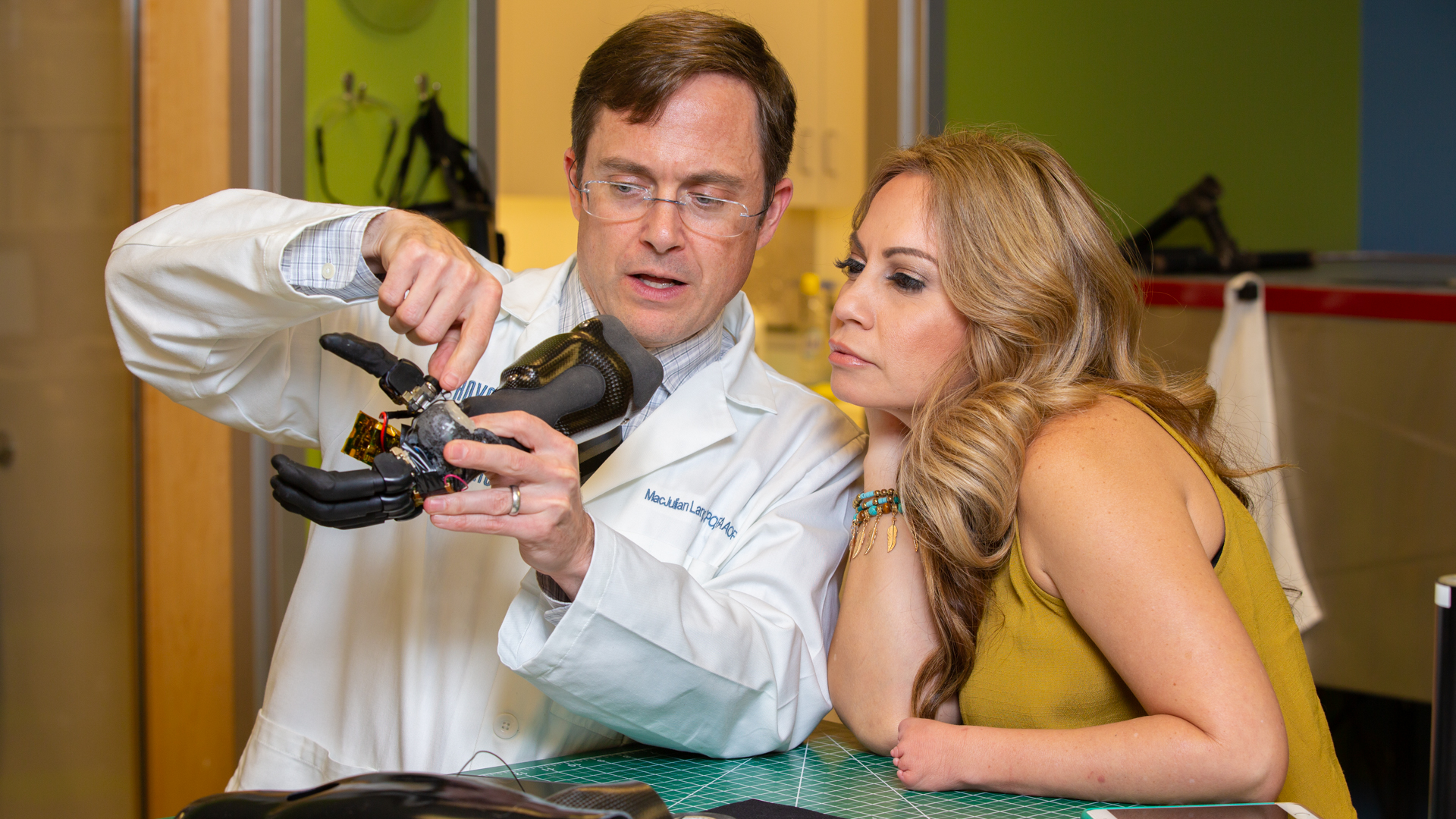 Prosthetist working with patient on electrically-powered partial hand prosthesis