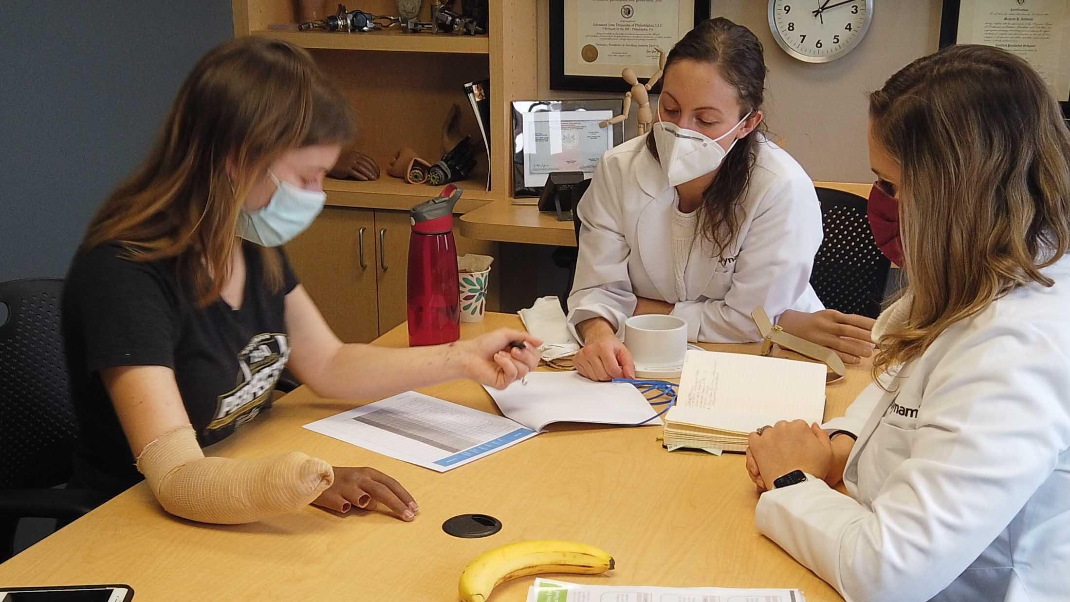 Michelle Intintoli, MSPO, CPO/L and Elyssa Vizzier, MOT, OTR/L work with a new patient