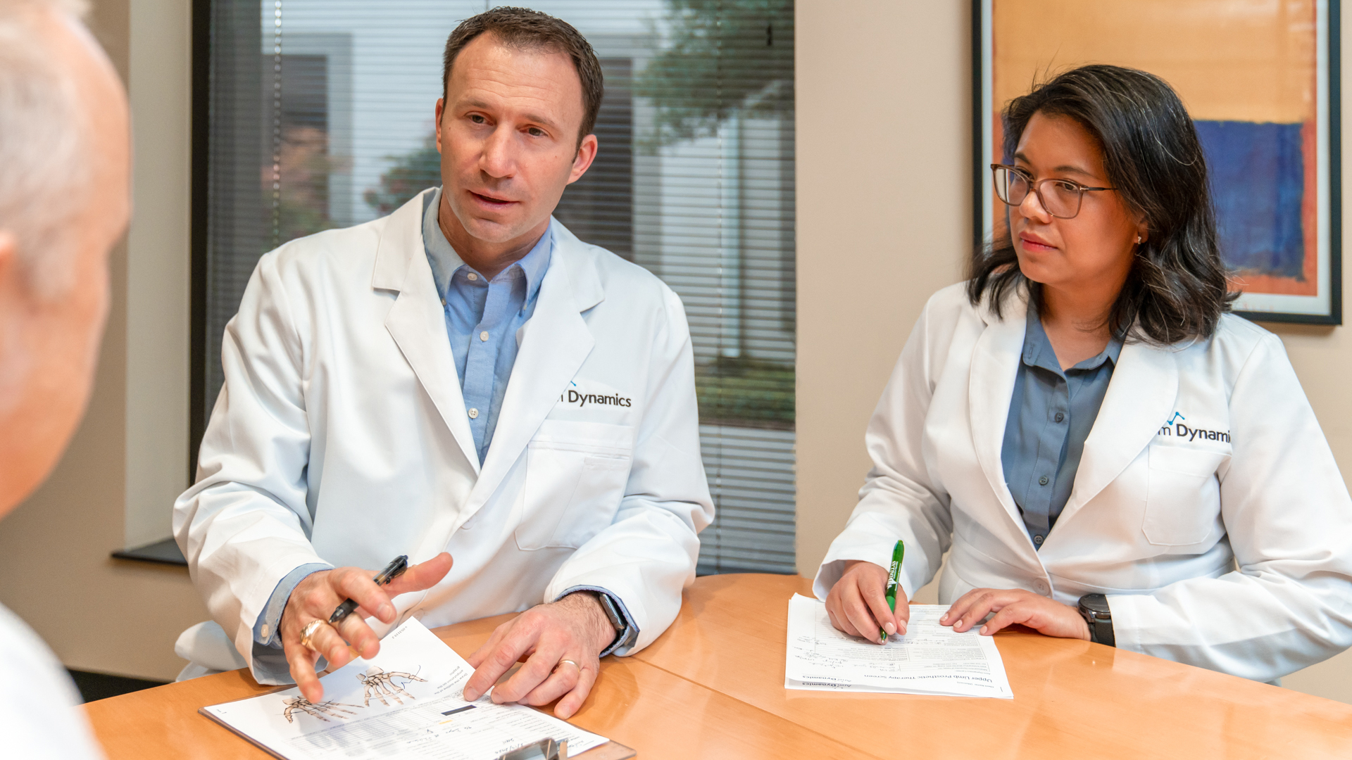Prosthetist Rob Dodson and Therapist Carina Hill at a consultation meeting with burn patient