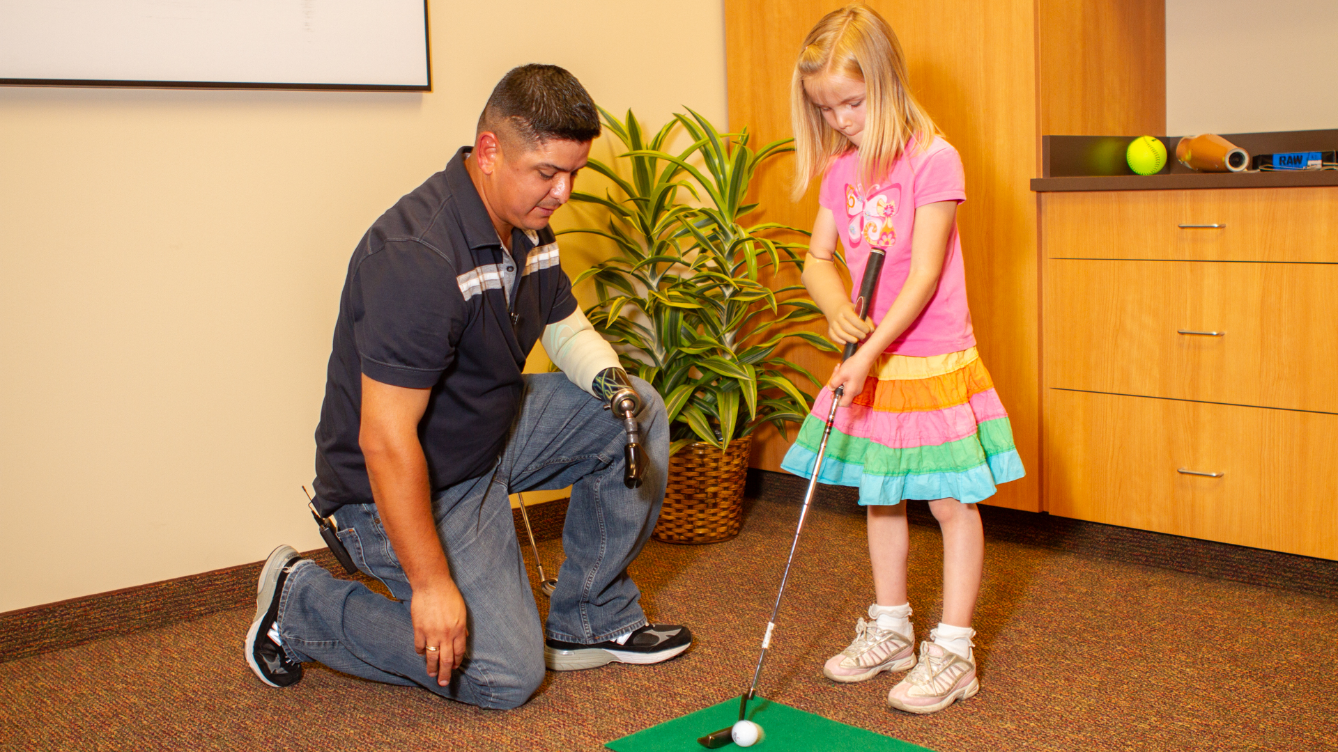 While in town on an event, Ramon Padilla works with pediatric patient Amber Peterson at her golf game.