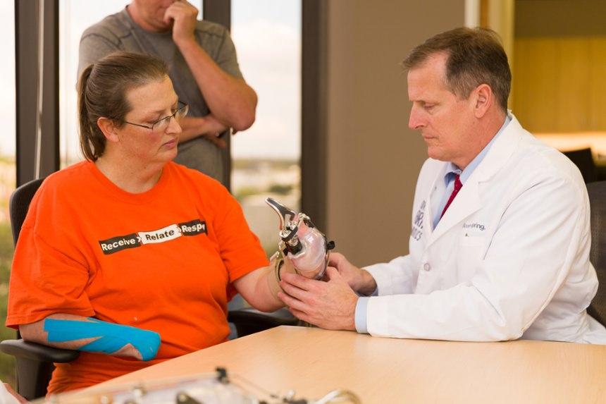 Prosthetist Scott Spring checks alignment of the prosthesis