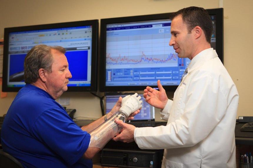 Prosthetist Rob Dodson checks alignment of the prosthesis